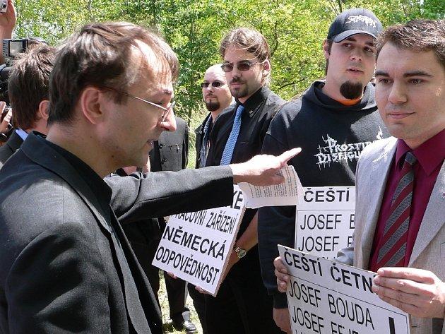 Incident. Přítomnost členů Národní strany hodně popudila německého novináře Markuse Pappeho, který na fotografii razantně vykazuje demonstrující z prostoru pietního místa. Vpravo proti němu stojí mluvčí demonstrantů Leoš Vacek.