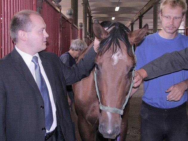 Ošetřovatel Ondřej Vojta drží koně, kterého hladí poslanec Michal Hašek.