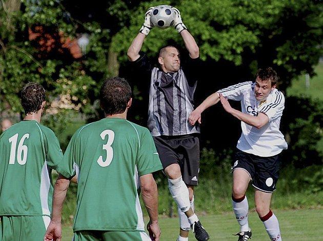 Domácí brankář Roman Jelínek chytá ve výskoku míč před dotírajícím Davidem Pichlíkem v utkání minulého kola krajského fotbalového přeboru, ve kterém Čížová hrála s Pískem B 0:0.