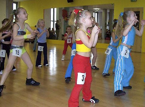 PĚKNÉ VÝKONY. Na snímku jsou dívky klubu Edita AK při finálovém cvičení, ve kterém  zcela ovládly stupně vítězů v kategorii 6 – 7 let. Jsou to: třetí v pořadí Adéla Filařová (č. 15), druhá Nikola Kdolská (č. 2) a první Barbora Vošahlíková (č. 6).