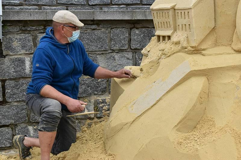 """Akademický sochař Josef Faltus při práci, lidé mu prý často závidí """"hraní"""" s pískem."""
