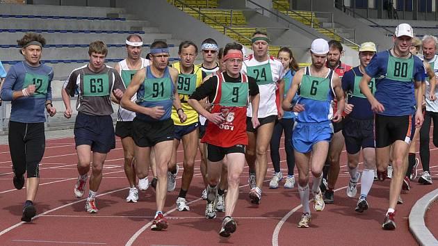 Běžci a běžkyně se po startu vydávají společně na trať závodu Písecká hodinovka, který se konal na píseckém atletickém stadionu.
