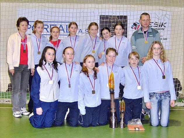 Na snímku je družstvo mladších žaček (s trenérem Janem Slavíkem a s vedoucí družstva Irenou Slavíkovou) házenkářského oddílu TJ Sokol Písek, které se na Prague Handball Cupu stalo v silné mezinárodní konkurenci vítězem turnaje v této věkové kategorii.