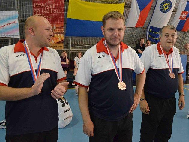 Trenér píseckých házenkářek Jan Slavík (uprostřed) s bronzovou medailí.