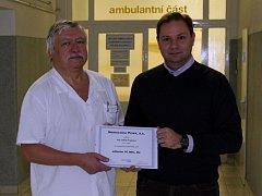 Vítěz soutěže Lukáš Tryml (vpravo) daroval výhru píseckému dětskému oddělení. Na snímku ji předává primáři oddělení Karlu Chytrému.