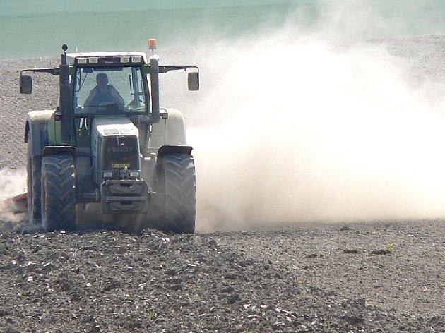 Při orbě se za traktory zdvihají mračna prachu...