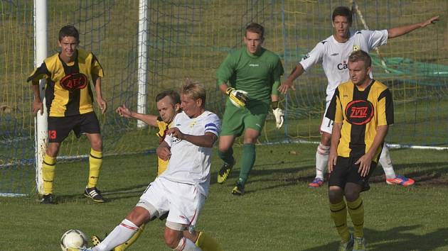 Kapitán hostujícího týmu Jan Zušťák (v bílém), kterého atakuje Radek Fiala, přispěl dvěma góly k vítězství mužstva FC Písek v utkání fotbalové divize v Milevsku v poměru 3:0.