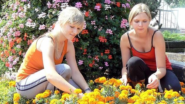 Květinový záhon na snímku upravují (zleva) Andrea Lišková a Lenka Beranová z Bud, které jsou zde na letní brigádě.