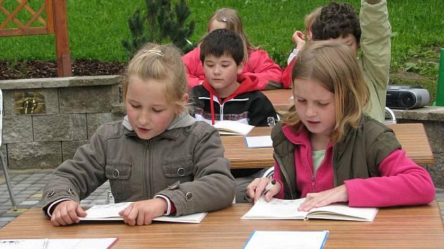 NA ČERSTVÉM VZDUCHU.  Při slavnostním otevření venkovní učebny žáci třídy 3. B příchozím předvedli, jak umí číst. Ukázka kvůli nepříznivému počasí trvala jen chvíli.