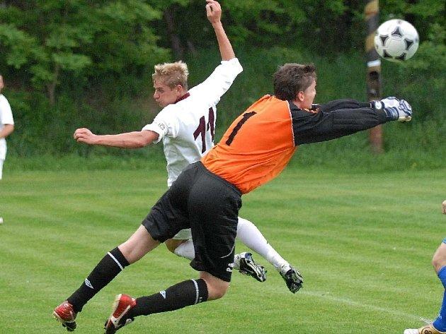Domácí brankář Smejkal vyráží míč před nabíhajícím kanonýrem Zušťákem v sobotním utkání krajského fotbalového přeboru, ve kterém tým Bavorovic podlehl doma mužstvu FC Písek 0:2.