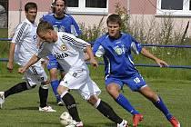 Hostující Martin Malý (u míče) uniká Příhodovi v utkání prvního kola fotbalového Ondrášovka Cupu, ve kterém divizní Třeboň prohrála s třetiligovým Pískem 0:2.