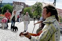 Josef Šindelář z Přebořic u Příbrami se na svém čundru po jižních Čechách zastavil s kytarou na Kamenném mostě. Kolemjdoucím hrál lidovky, ale i známé novodobé písně. Prý proto, že mu Kamenný most evokuje pražský Karlův, kde je pouliční umění běžné.