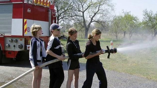 Mimo program. Díky návštěvě hasičů si mohli někteří účastníci kurzu vyzkoušet, jak je obtížné hasit požár.