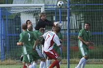 Brankář hostí Pavel Rams vyráží míč před dotírajícím Michalem Polodnou v zápase úvodního kola fotbalové divize, ve kterém Votice zvítězily nad Čížovou 2:1.