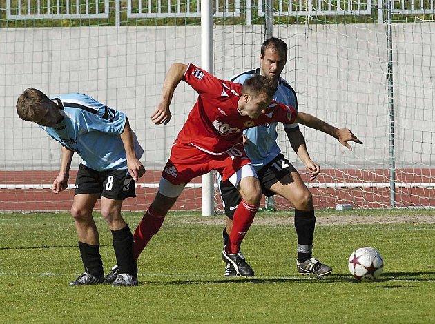 Domácí Aleš Červenka (v červeném) bojuje o míč s Vonešem (vlevo) a Dvořákem v utkání krajského fotbalového přeboru, ve kterém FC Písek B zvítězil nad Dražicemí 2:1.