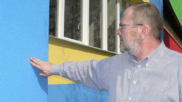 Ředitel školy Karel Bican ukazuje poškozenou zeď