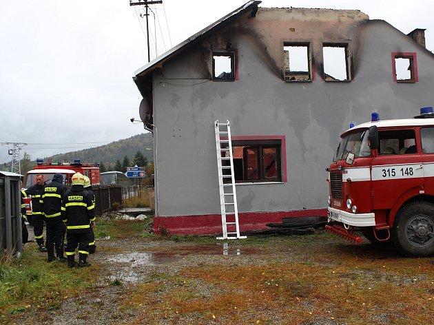 Lenorští hasiči u vyhořelého domu drží hlídku během celého úterka.