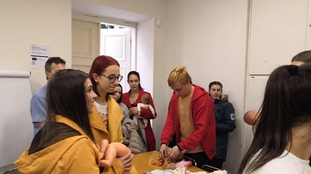 Prachatičtí dobrovolníci vybírají panenky a látky na jejich nové oblečky.