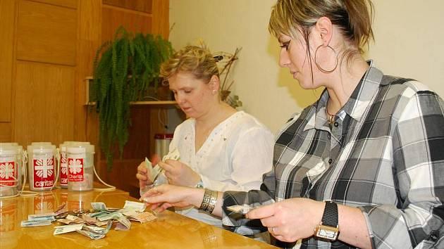 Pracovnice charity počítají výtěžek z Tříkrálové sbírky.