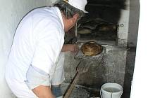 Pekař Augustin Sobotovič sází do pece chléb