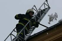 Hasiči odstraňují sníh ze střech.