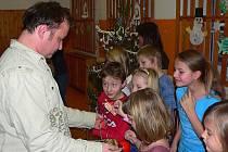 Ředitel Jícha předává dětem dárky.