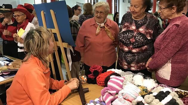 Dobrovolníci a návštěvníci KreBul vlastnoručně vyrábějí věci, které jsou ke koupi v okně v ulici Zlatá stezka.
