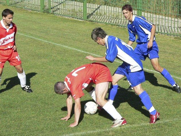 Domácí Tesárek bojuje o míč s útočníky Tábora.