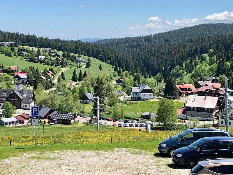Turisté zaparkují a vyrážejí do šumavských lesů, ve Kvildě se příliš nezdrží.