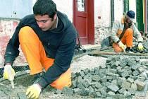 V PLNÉM PROUDU.  V ulici Husova pracují dělníci pilně na položení dlážděného povrchu. V jejich očích je vidět obrovské nasazení.