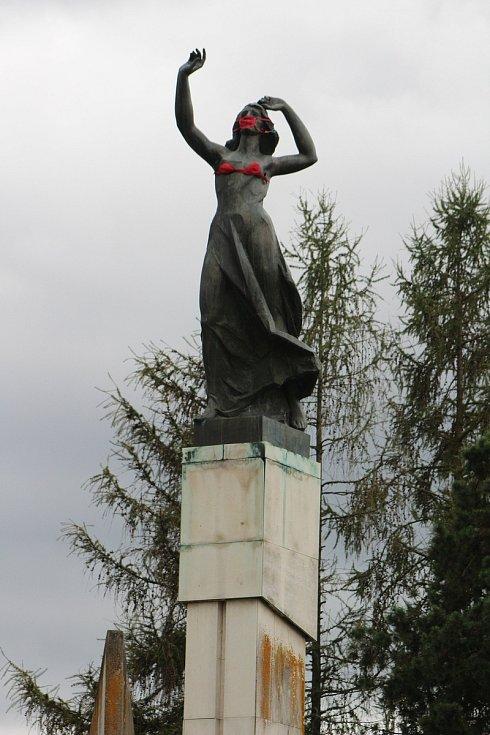 """Socha přezdívaná """"Stopařka"""" na křižovatce u Vitějovic má ústa zahalená červenou rouškou. Outfit doplnil neznámý recesista také červenou podprsenkou."""