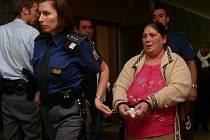 Osouzenou ženu odvádí vězeňská stráž.