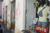 Po nájezdu neznámého vandala zůstaly zdemolované výkladní skříně a pokreslená zeď.