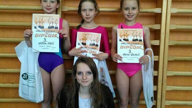 Vimperským gymnastkám se zadařilo. Zleva Kateřina Horová, Ester Ollé a Adriana Košnarová. Pod nimi trenérka Blanka Vašurová.