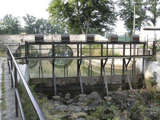 Na snímku je most (v pozadí za stavidly), přes který přejíždějí řidiči nákladních vozidel, a tím jej poškozují.