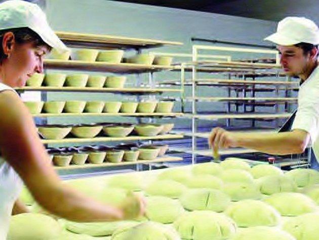 ZATÍM CENY DRŽÍ. Ve vlachovobřezské pekárně zatím ceny nezvedali, čekají, jak podraží mouka. Na snímku sázejí chléb do pece Jana Rapčaniová a Radek Vach.