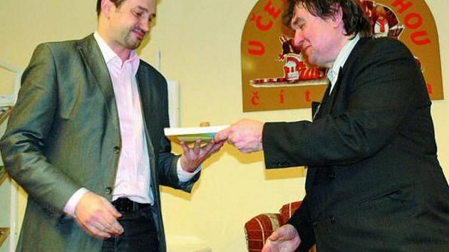 KŘEST. Symbolicky položil špunt od lahve šampaňského na novou knihu místostarosta Prachatic Martin Malý (vlevo).