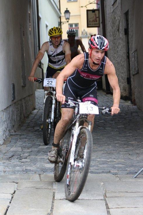 Hlavní závod se dostal na Velké náměstí v Prachaticích. Závodníci vjíždějí do druhého kola cyklistické části hlavního závodu.
