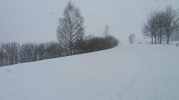 Sněhové přeháňky, vydatné sněžení v kombinaci se silným větrem dělají ze silnic ve vyšších polohách Prachaticka sněhové pláně.