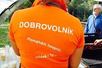Dobrovolníci v oranžových tričkách.