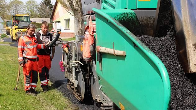 Pokládání asfaltu na silnici z Vacova do Vrbice.