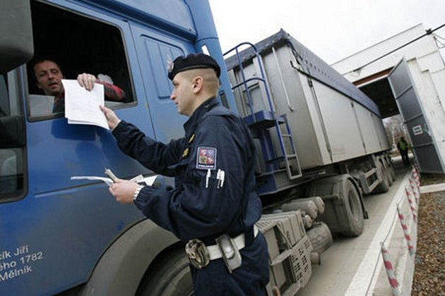 Policisté kontrolují váhu kamionu. Jejich přetěžování vede k poškozování povrchu vozovek.