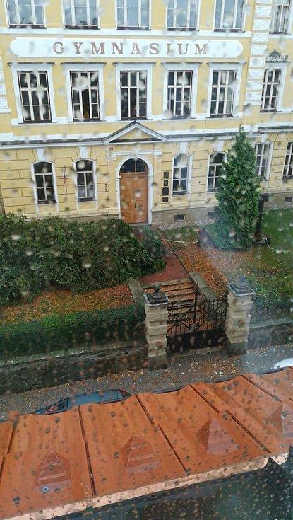Vyvalený plot a poškozená 2 auta. Navíc některá okna jsou v budově gymnázia otevřená.