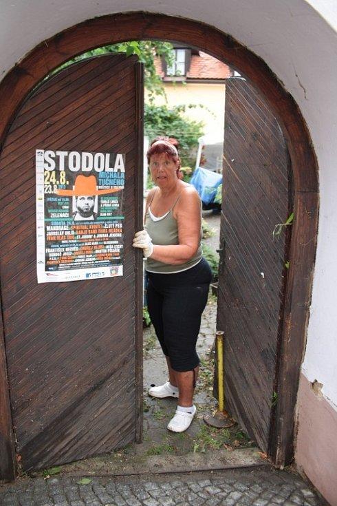 Zdeňka Hrůzová otevírá do zahrady v Solní ulici, kde po bouřce zůstal nepořádek a zničené květiny.