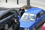 Mladík se podezřele dobýval do kufru modré škodovky.