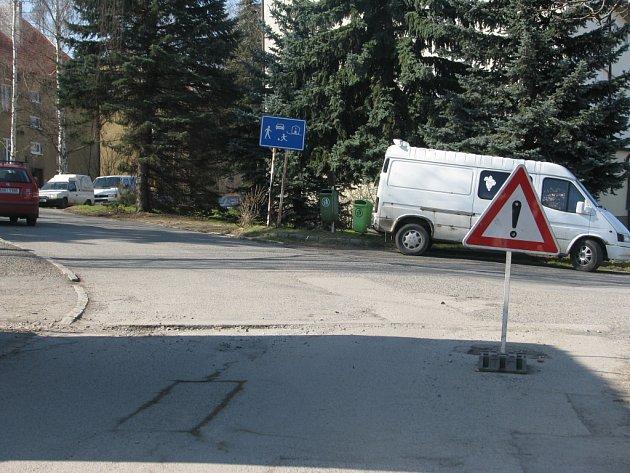 Dopravní cedule stojí ve vozovce.