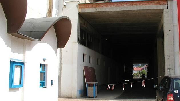Oprýskaný vchod zimního stadionu v kontrastu s novým aquaparkem.