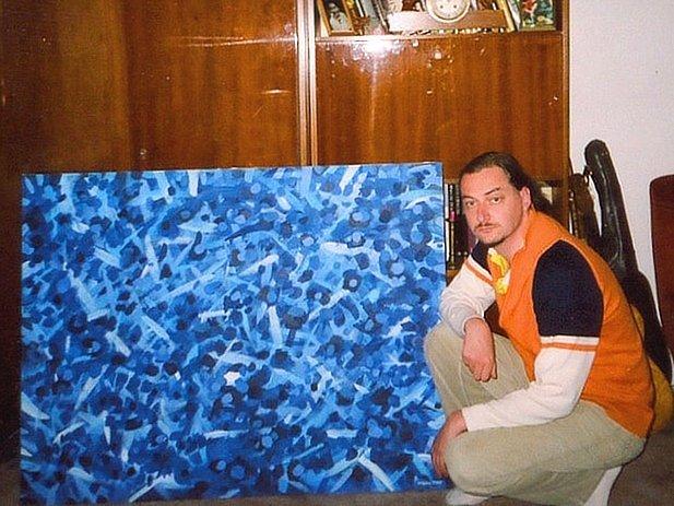 Tomáš Petříček u jednoho z vystavených obrazů.