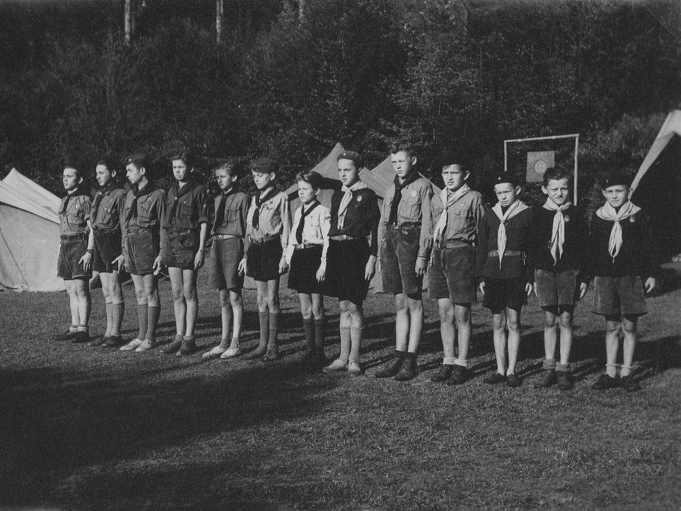 Junák Komárov (1945 - 1948). Skautský tábor u Podmokelského mlýna (1946): táborníci na nástupu. Na fotografii zleva: první Sáša Křikava, druhý Zdirad Mraček, třetí Ladislav Hodek, šestý Korejčík a sedmý Václav Zeman.