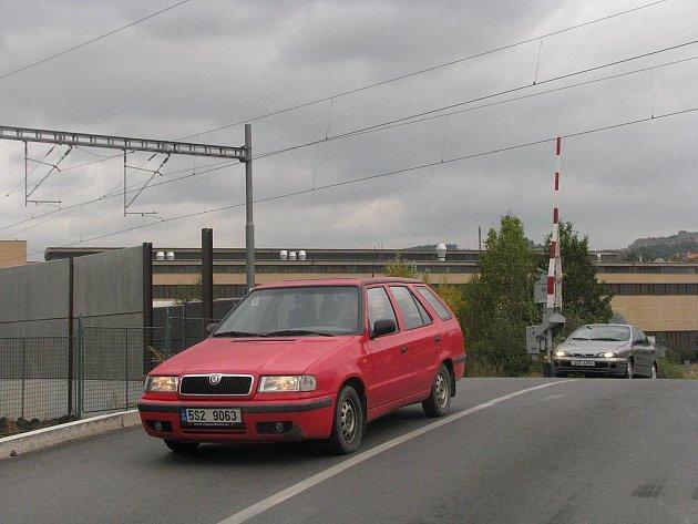 Trať u železničního přejezdu lemují betonové zdi 2,5 metru vysoké